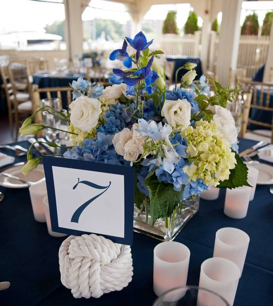 a nautical wedding centerpiece of white and blue blooms and greenery, a rope knot and candles is a stylish and timeless idea
