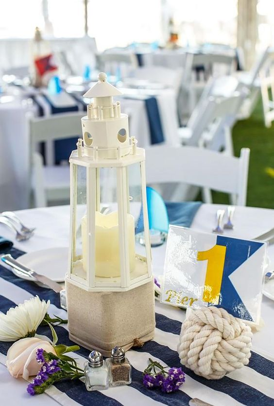 a nautical wedding centerpiece with a beacon candle lantern, a rope number stand, blooms on the table