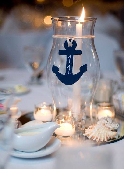 a nautical wedding centerpiece with candles, seashells, a candle lantern with a navy anchor is a lovely idea for a nautical wedding