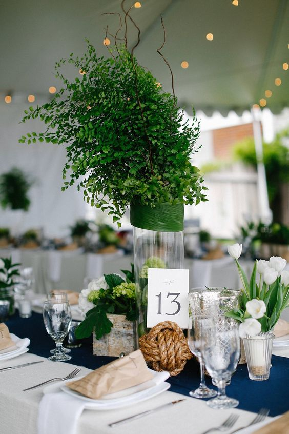a nautical wedding table setting with white linens, a navy table runner, a rope knot, a greenery arrangement and white tulips is chic