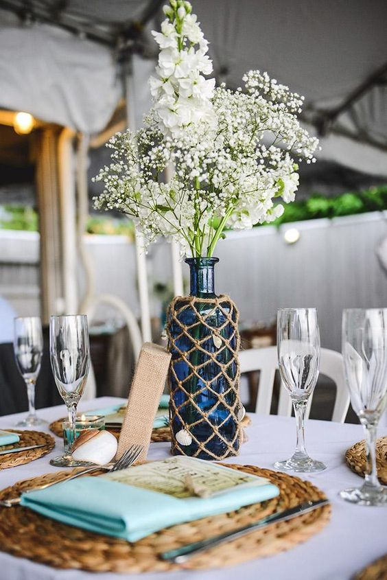a nautical wedding table setting with woven chargers, turquoise napkins, a blue bottles in a net and white blooms is chic