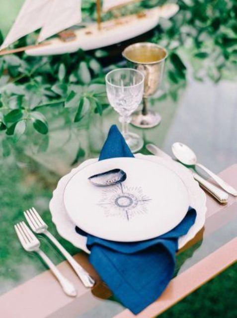 a nautical wedding tablescape with a glass table, a nautical plate, greenery and a boat, navy napkins is modern and cool