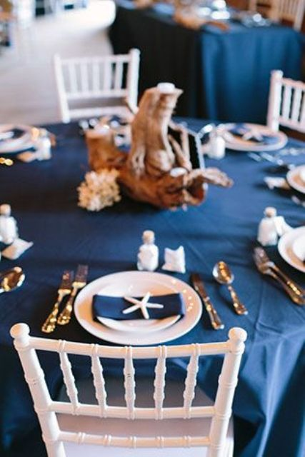 a nautical wedding tablescape with a navy tablecloth and napkins, starfish and corals, driftwood and seashells