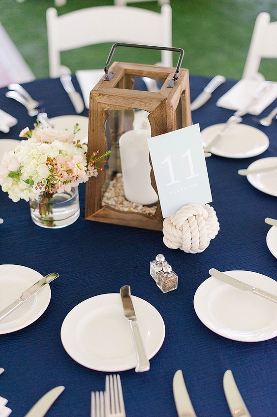 a nautical wedding tablescape with a navy tablecloth, white plates and silver, a wooden candle lantern, neutral blooms and a roper knot