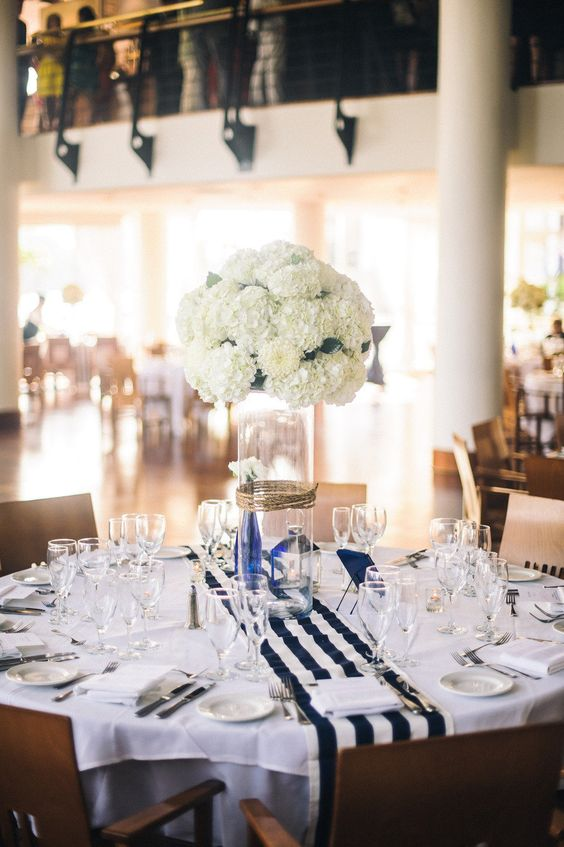 a nautical wedding tablescape with a white tablecloth, a striped runner, a lush white hydrangea centerpiece and white porcelain