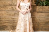 a neutral A-line wedding dress with gold stars and moons, with a train and black spaghetti straps is a very refined idea for a celestial bride