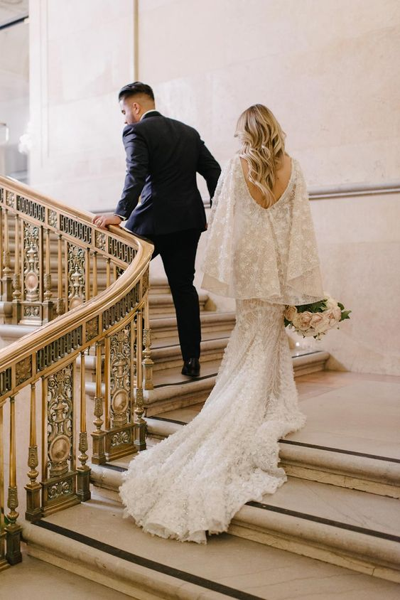 a neutral fitting wedding dress with a long train, a cutout back, a capelet - all covered with embroidered stars is wow