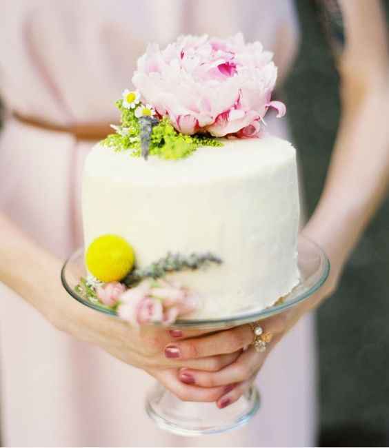 a one tier buttercream wedding cake with greenery, a pink peonyand a billy ball is a stylish and chic idea for spring or summer