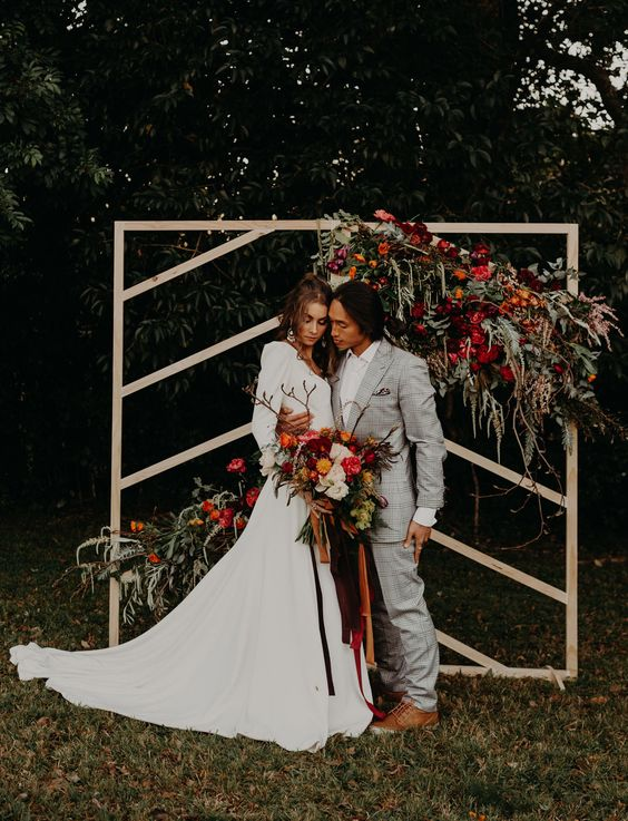 a plywood wedding backdrop decorated with greenery and super bold blooms is a lovely idea for a mid-century modern wedding