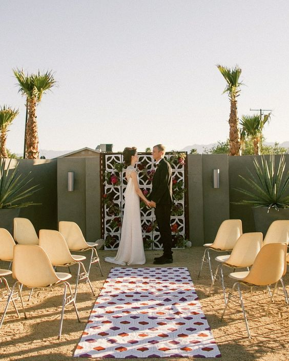 a pretty mid-century modern wedding backdrop decorated with bright blooms and greenery, with a printed rug and yellow chairs