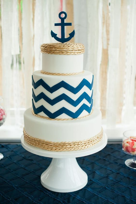 a pretty nautical wedding cake with navy chevrons, gold rope and a navy anchor on top is an amazing idea for a seaside wedding
