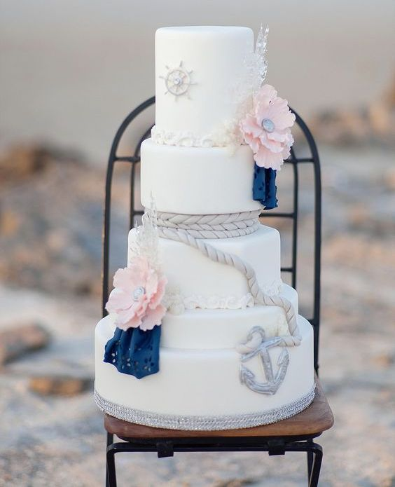 a pretty nautical wedding cake with white tiers, pink sugar blooms and navy doilies, rope and anchors is bold and cool