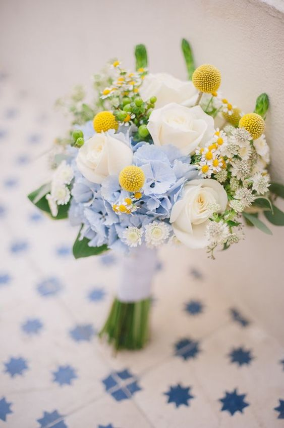 a pretty wedding bouquet with white roses, blue and white blooms, billy balls and greenery for spring