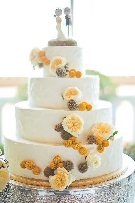 a pretty white buttercream wedding cake with peachy peonies, seed pods, billy balls and a funny cake topper for spring or summer
