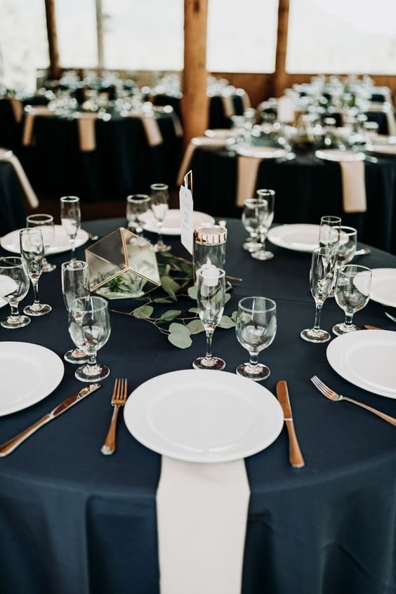 a refined and elegant nautical wedding tablescape with a navy tablecloth, white napkins, greenery and a cube plus candles