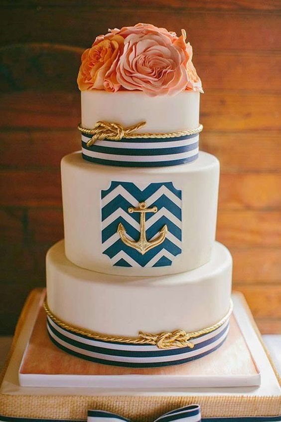 a refined nautical wedding cake with navy stripes and chevrons, gold roper and an anchor, coral blooms is a chic idea for summer
