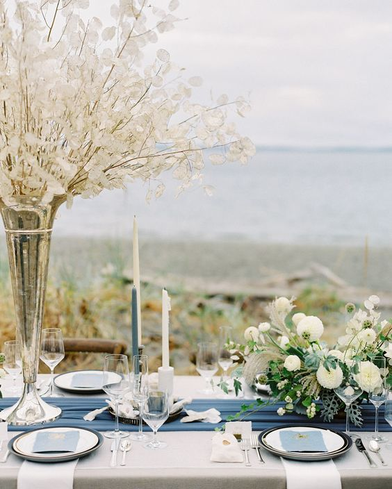 a refined nautical wedding table setting with neutral linens and a navy table runner, blue and white candles, lunaria branches and white blooms