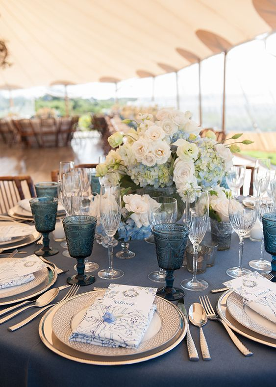 a refined nautical wedding tablescape with a navy tablecloth, gilded chargers and cutlery, white and blue blooms and blue glasses