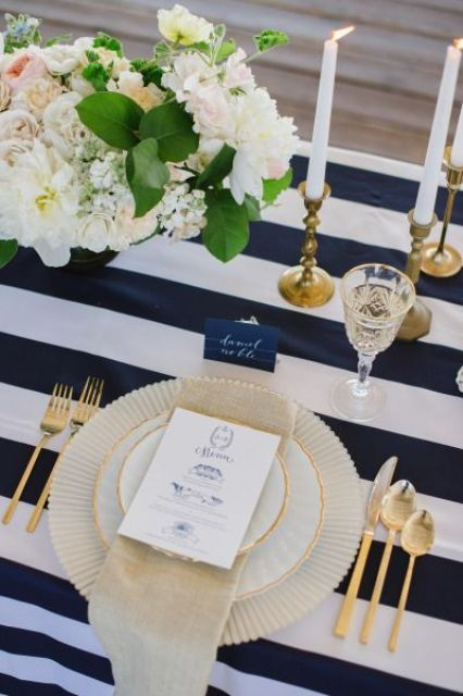 a refined wedding tablescape with a navy and white striped tablecloth, neutral and blush blooms and greenery, touches of gold