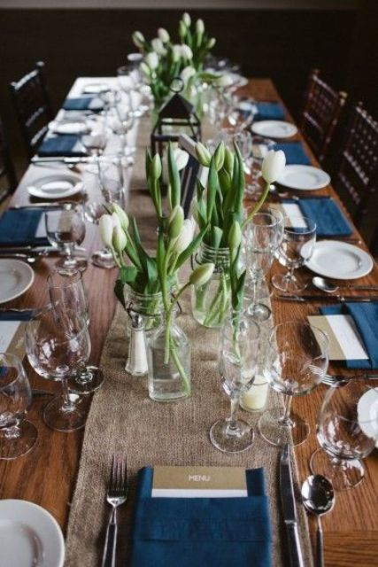 a rustic nautical wedding tablescape witha burlap runner, white tulipes, navy napkins and two tone menus plus candles