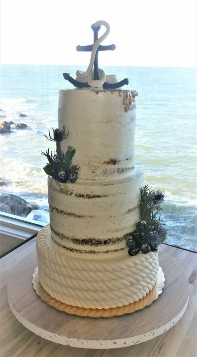a semi-naked wedding cake with a rope tier, some greenery, an anchor and rope on top is a lovely and chic idea to rock