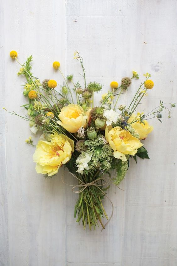 a simple and lovely wedding bouquet with yellow and white blooms, billy balls and greenery plus seed pods is an amazing idea