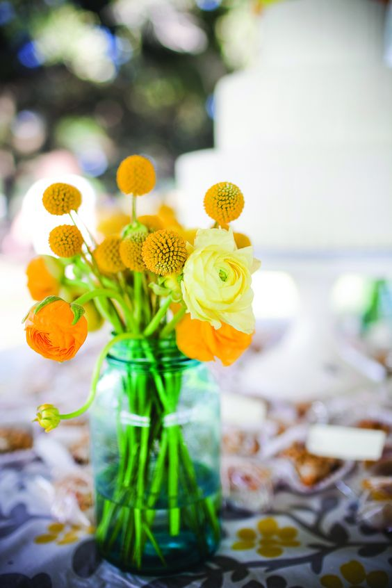 a simple and stylish billy balls and orange and yellow ranunculus wedding centerpiece for a summer wedding
