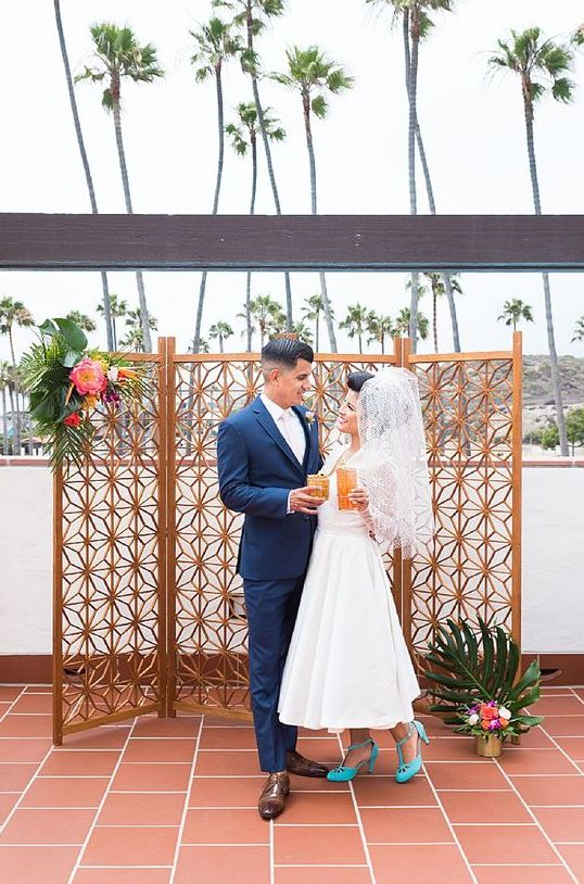 a simple laser cut screen wedding backdrop, tropical leaves and bold blooms for a bright mid-century modern wedding