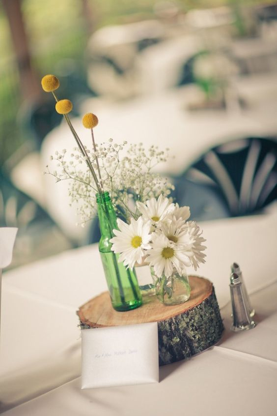 a simple rustic wedding centerpiece of a wood slice, white daisies, baby's breath and billy balls is an easy idea