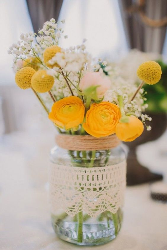 a simple rustic wedding centerpiece of yellow blooms and billy balls, blush roses and baby's breath in a jar wrapped with twine and lace
