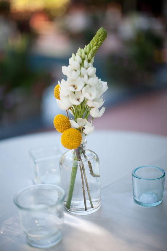 a simple spring or summer wedding centerpiece of billy balls and a white blooming branch is a pretty idea to rock