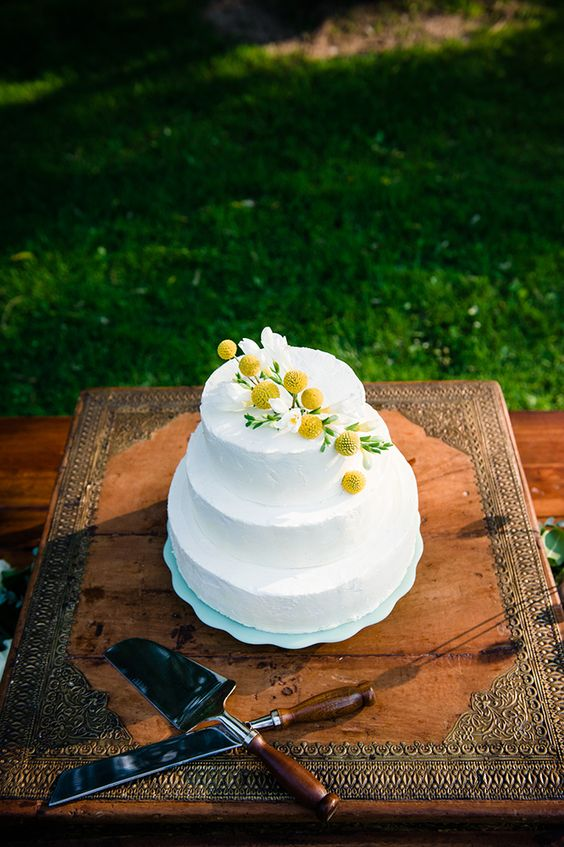 a sleek white buttercream wedding cake topped with white blooms and billy balls plus greenery is an amazing idea for summer
