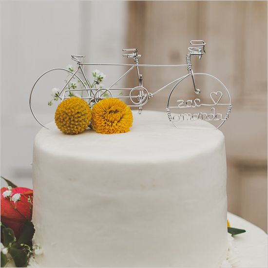 a sleek white wedding cake with billy balls and a pretty bike cake topper for a couple who enjoy riding bikes