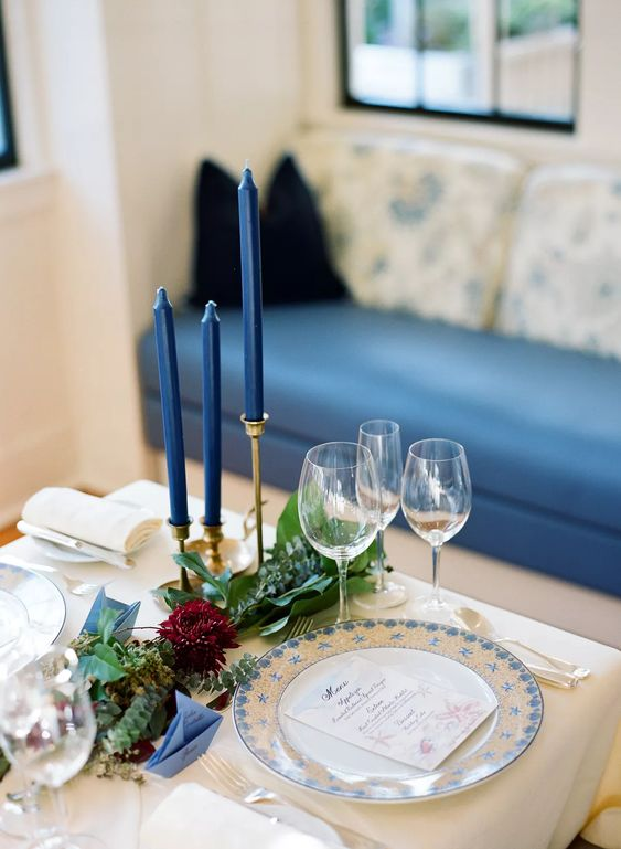 a sophisticated nautical wedding table setting with navy candles, a blue patterned plate, greenery and burgundy blooms and neutral linens