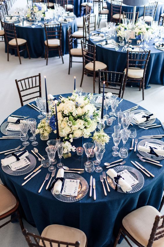 a sophisticated nautical wedding tablescape with a navy tablecloth, white napkins and menues, navy candles and a lush floral centerpiece