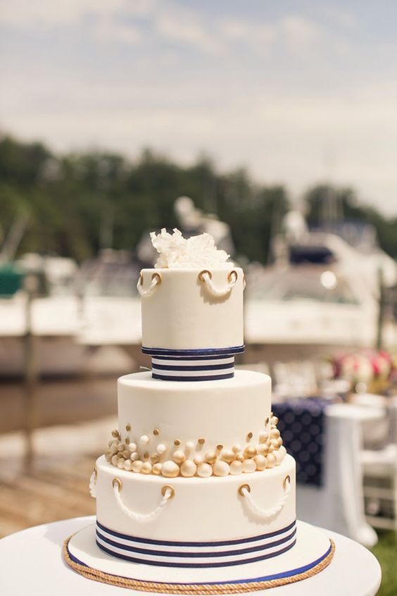a sophisticated wedding cake with navy stripes, pearls and polka dots, rope and a white sugar bloom on top