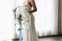 a sparkling mermaid wedding dress with straps, a deep neckline and a train, is fully embellished and sparkling