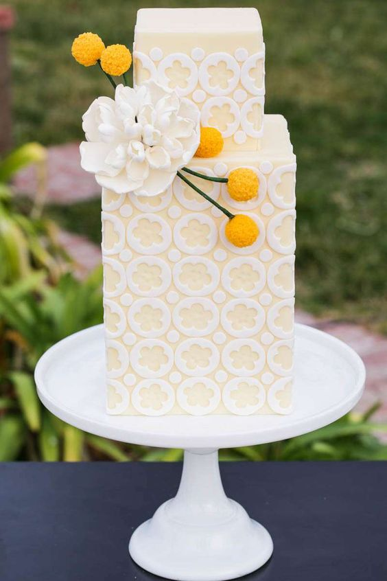 a square yellow and white buttercream wedding cake with a white bloom and billy balls is a beautiful and chic modern idea