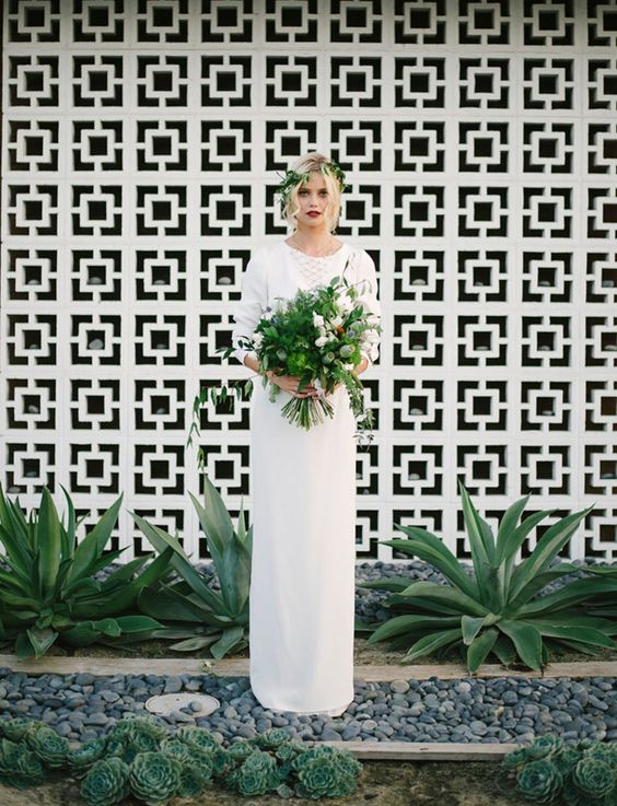 a stylish geometric wall and living plants as a natural and cool mid-century modern wedding backdrop is a lovely solution