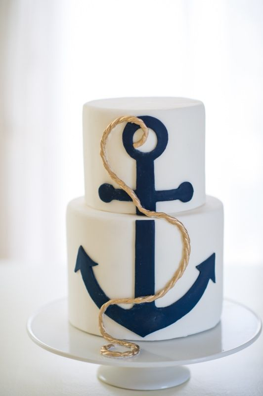 a stylish nautical wedding cake in white, with a large navy anchor, gold rope is an amazing idea to rock for your seaside wedding