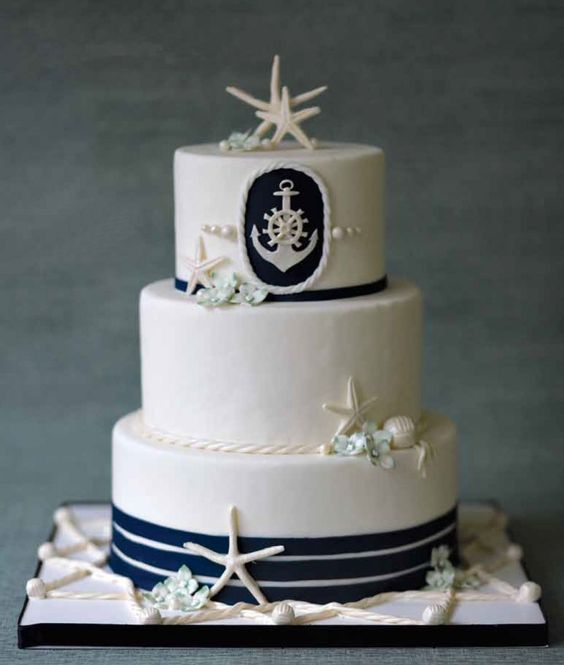 a stylish nautical wedding cake with navy stripes, starfish, seashells and pearls plus an anchor piece for decor is amazing