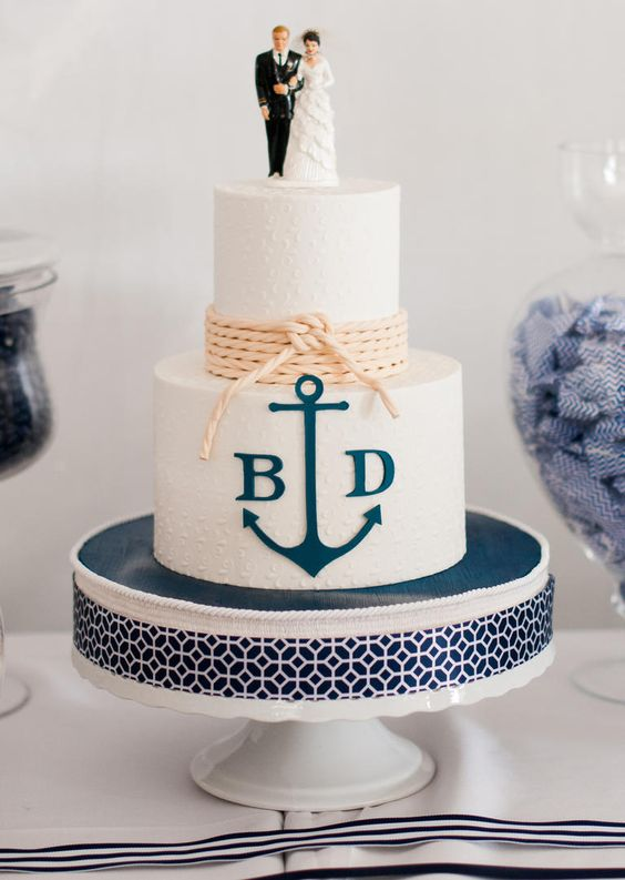 a stylish nautical wedding cake with white textural buttercream, a navy anchor and monograms, neutral rope and lovely cake toppers