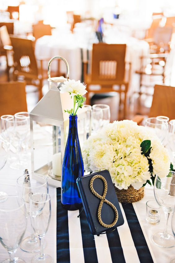 a stylish nautical wedding centerpiece of a candle lantern, a navy bottle with white blooms and a matching centerpiece in a vase, a navy wood and rope table number