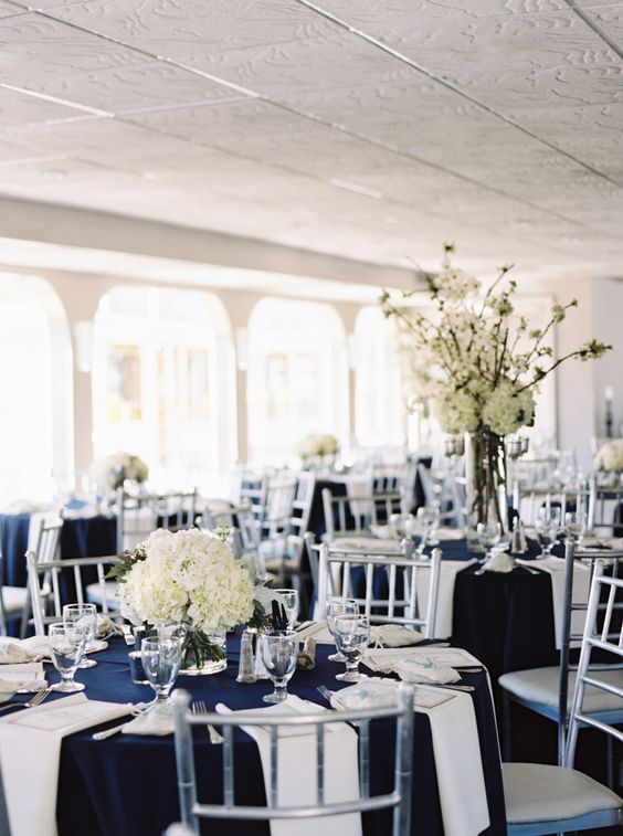 a stylish nautical wedding table setting with a navy tablecloth and white napkins, white hydrangeas and silver cutlery