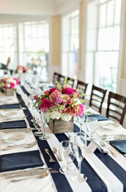 a stylish nautical wedding tablescape with a striped runner and navy napkins, bold pink florals and greenery is a chic and cool idea