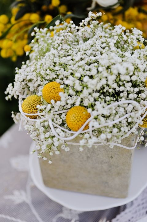 a stylish wedding centerpiece of concrete, with billy balls and baby's breath is a cool idea for spring or summer