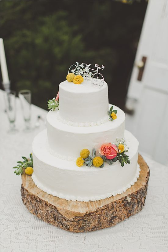 a stylish white buttercream wedding cake with a coral rose, billy balls and greenery and a pretty bicycle wedding cake topper