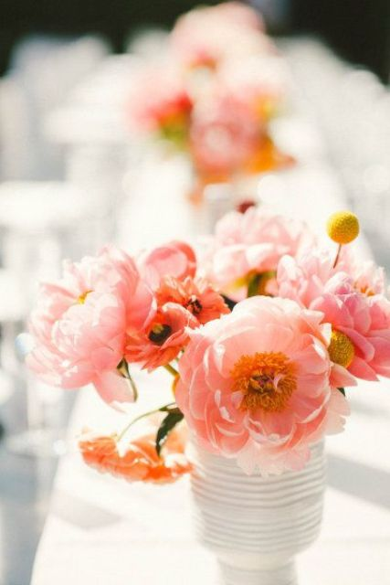 a summer wedding centerpiece of coral and red blooms and billy balls is a bright idea for a colorful summer wedding