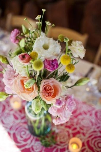 a summer wedding centerpiece of pink and peachy blooms, white flowers, greenery and billy balls is a bright and cool idea