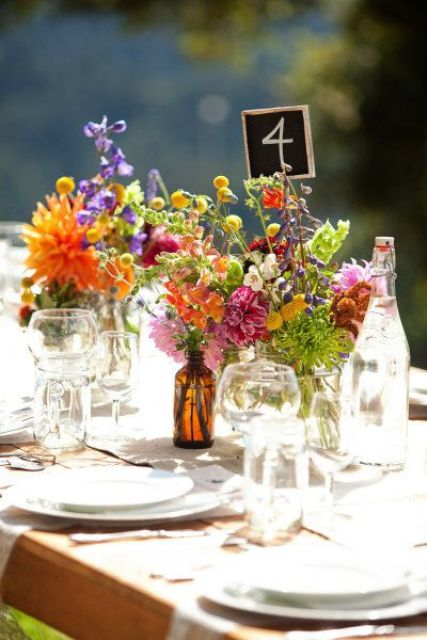 a super colorful and simple wedding centerpiece of pink, orange, yellow, purple and red blooms and greenery for a wildflower wedding